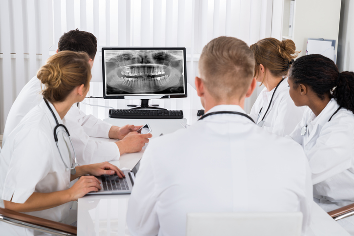Group Of Doctors Looking At Teeth X-ray On Computer Desktop In Hospital