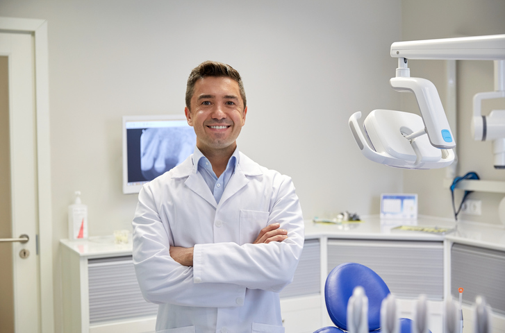 people, medicine, stomatology and healthcare concept - happy middle aged male dentist in white coat at dental clinic office