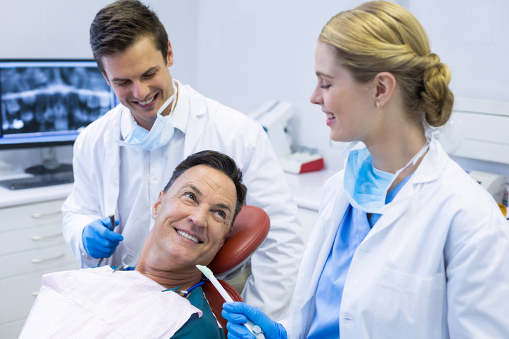 Dentists interacting with a male patient in clinic