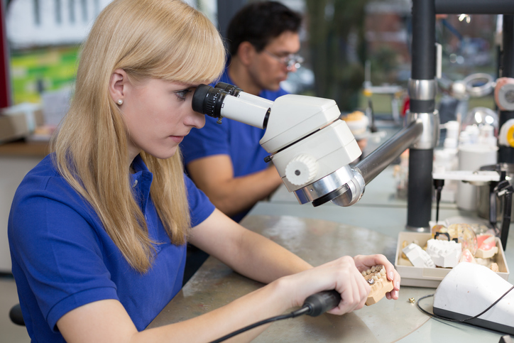 Dental technician producing a prosthesis under a microscope