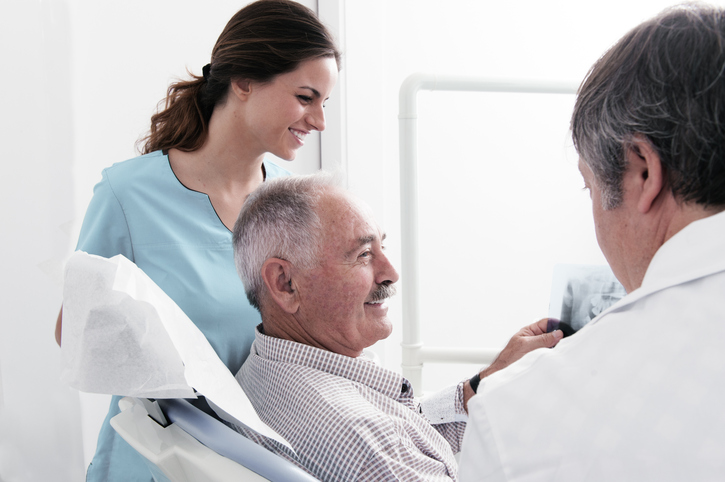 Dental Clinic. An elderly retired gentleman, discussing with your dentist x-ray results