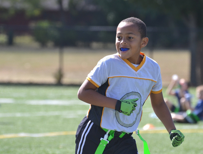 mixed race 9 year old boy loping on the flag football field, happy, autumn