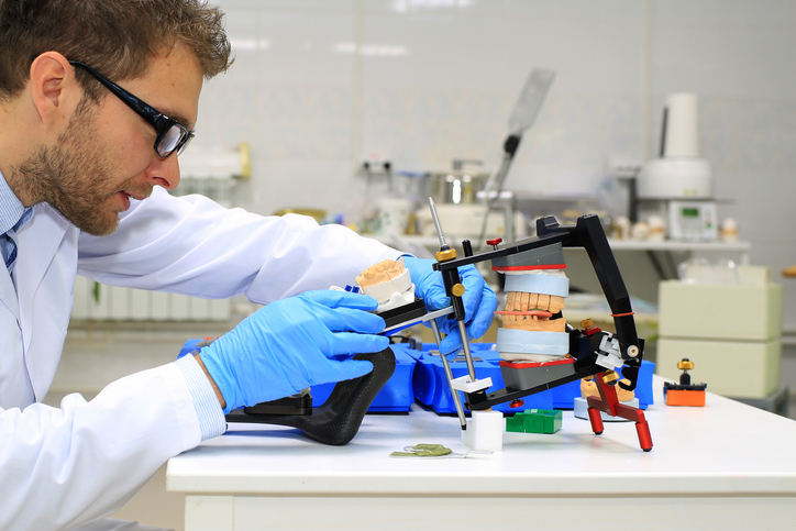 Dental technician checks his work in the lab