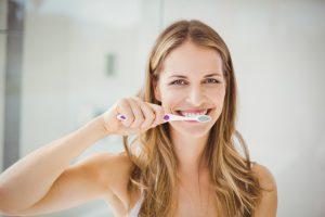 Portrait of beautiful young woman brushing teeth