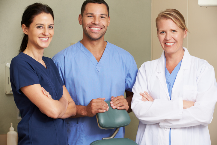 Portrait Of Dentist And Dental Nurses In Surgery Smiling To Camera